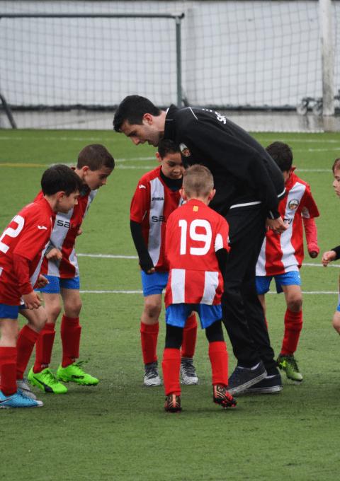 Valmentaja neuvomassa nuoria jalkapalloilijoita