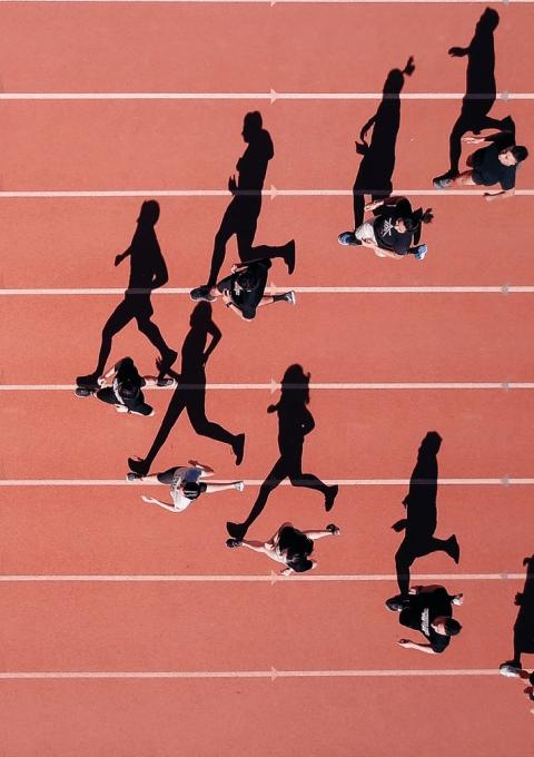 Juoksijoita juoksuradalla, kuvattu yläpuolelta